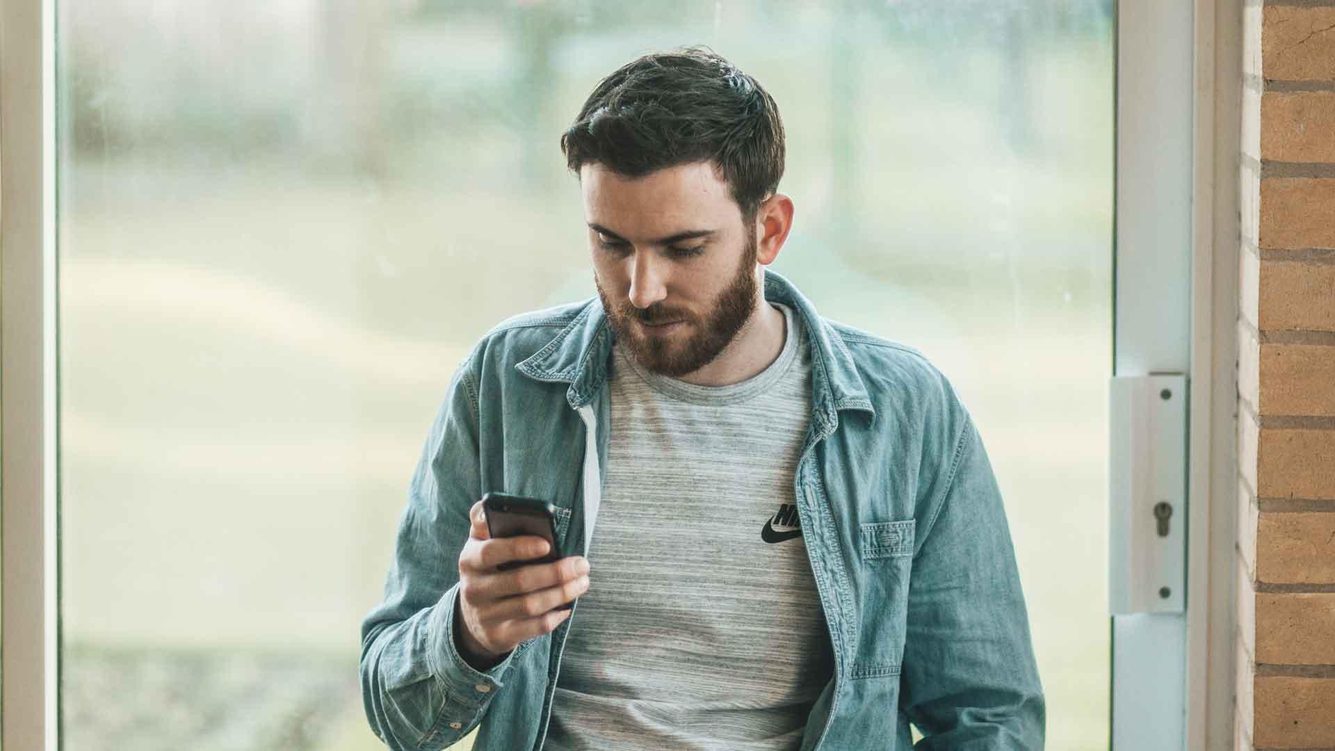 Mann im Anzug mit Smartphone in der Hand