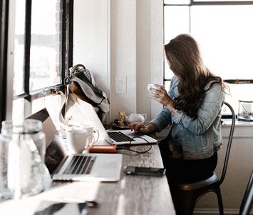 Frau sitzt im Büro am Laptop und trinkt aus einer Tasse