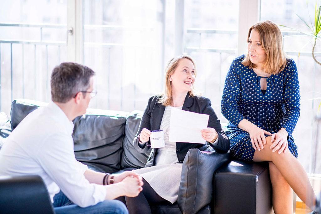 Zwei Frauen und ein Mann unterhalten sich und sitzen auf einem Sofa