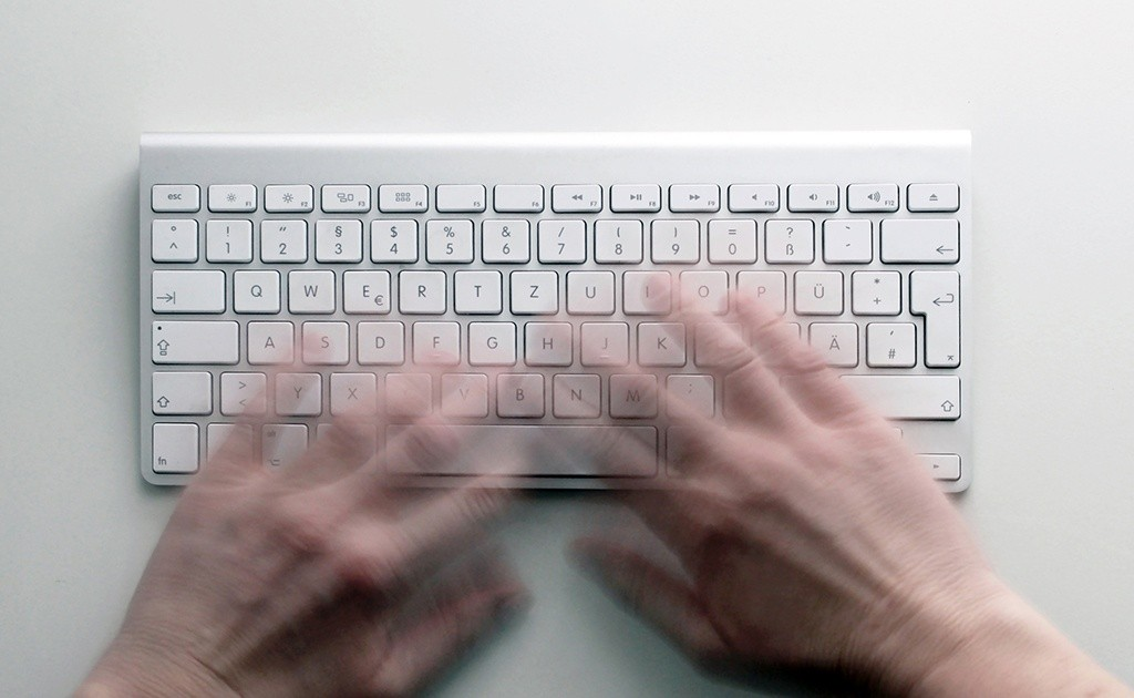 Person die an einer Tastatur schreibt