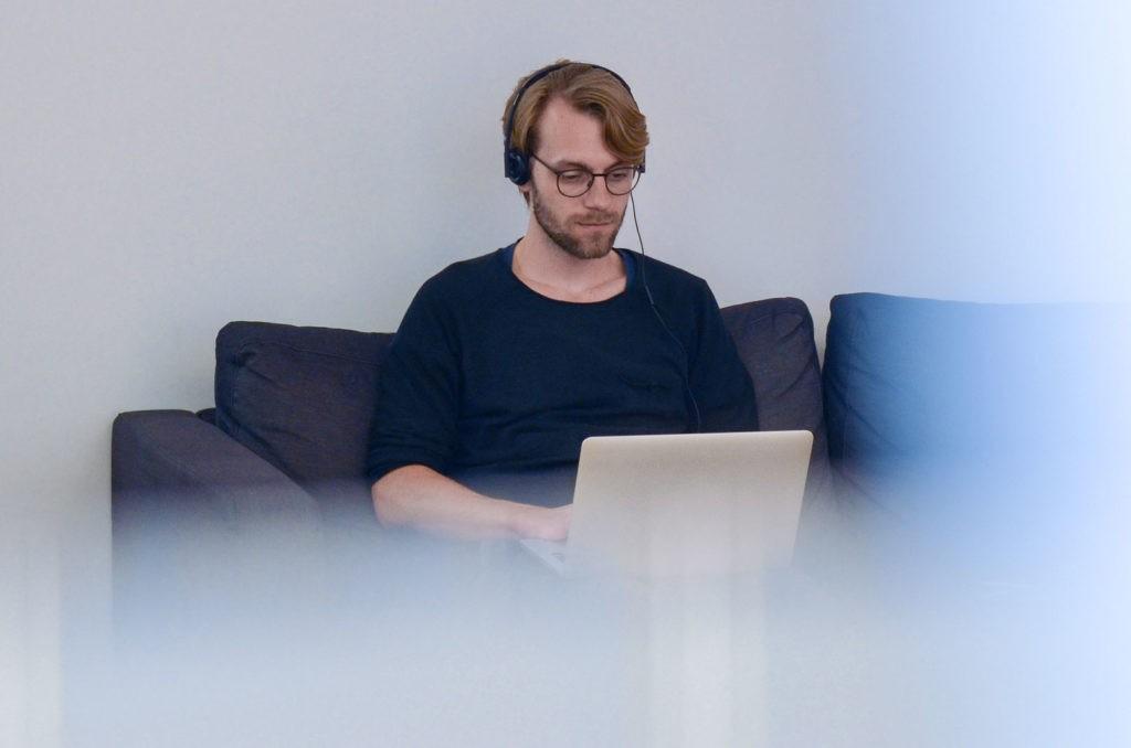 Ein Mann benutzt seinen Laptop und Headset für ein Video Interview