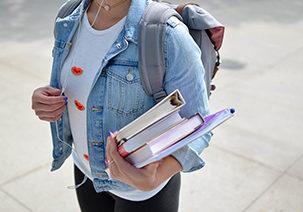 Junge Frau trägt Rucksack auf dem Rücken und hat Bücher in der Hand