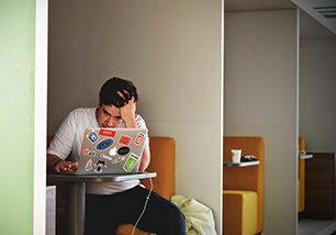 Junger Mann sitzt vor dem Laptop und stützt den Kopf mit der Hand ab